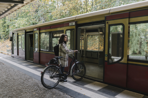woman with bicycle entering an underground