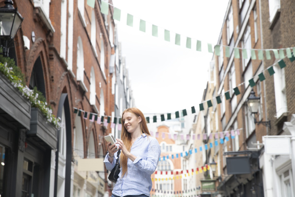 smiling young redhead woman using smart