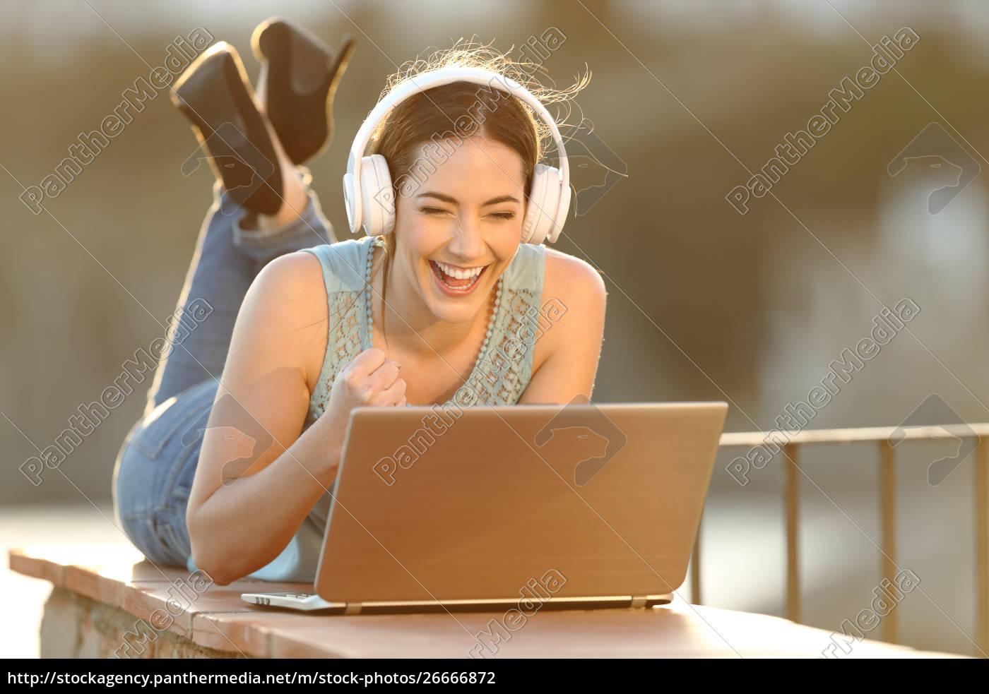 excited, girl, wearing, headphones, watching, media - 26666872
